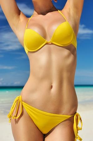 seni: Donna con bel corpo su una spiaggia tropicale