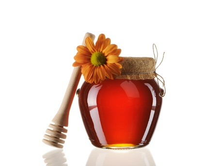 Jar of honey and dipper isolated over white Stock Photo