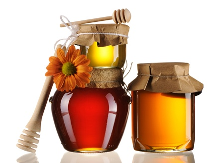 Jars of honey and dipper isolated over white Stock Photo - 8987296