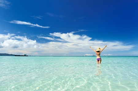 arms raised girl: Girl on a tropical beach with outstretched arms Stock Photo