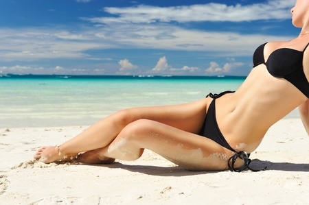 Woman with  beautiful body on a tropical beach photo