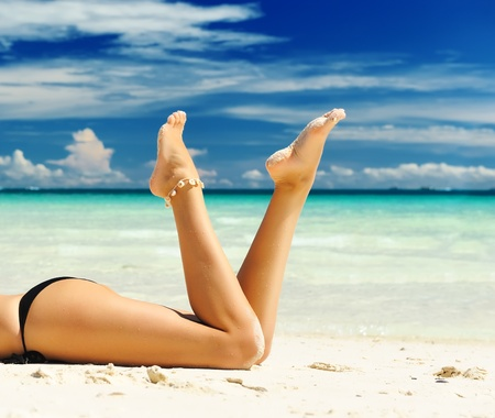 Womens beautiful legs on the beach photo