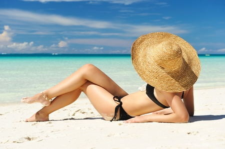 laying on back: Girl on a tropical beach with hat Stock Photo