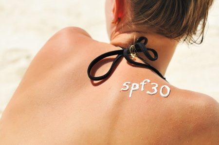 Sunscreen lotion over tan woman skin made as SPF 30 word photo