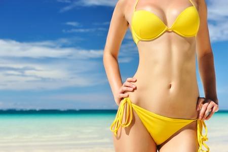 Femme au beau corps sur une plage tropicale Banque d'images