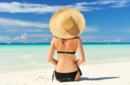 sexy girl sitting: Girl on a tropical beach with hat Stock Photo