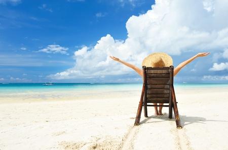 熱帯のビーチの帽子の少女