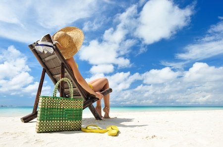 Girl on a tropical beach with hat Banque d'images