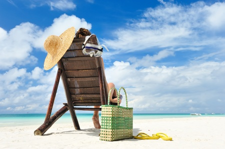 vacation destinations: Girl on a tropical beach with hat Stock Photo