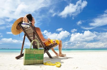 熱帯のビーチ帽子をかぶった男