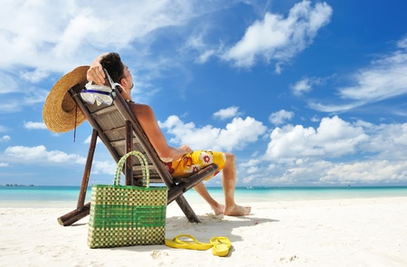 man in chair: Man on a tropical beach with hat
