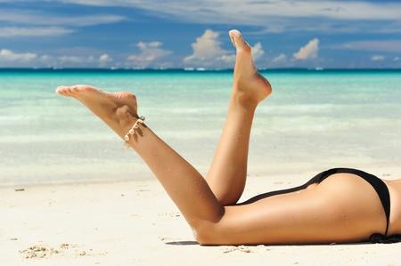 Hermosas piernas de la mujer en la playa Foto de archivo