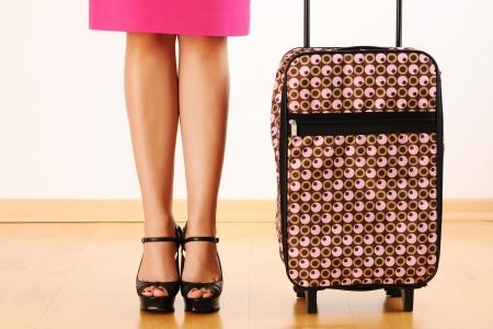 mujer con maleta: Maleta de viaje y las piernas de la mujer Foto de archivo