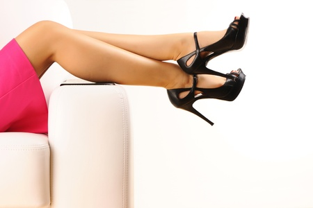 lying on couch: Woman with beautiful legs sitting on sofa Stock Photo