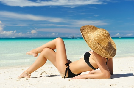 girl lying: Girl on a tropical beach with hat Stock Photo