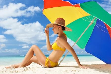 mujeres sentadas: Chica en una playa tropical con sombrero