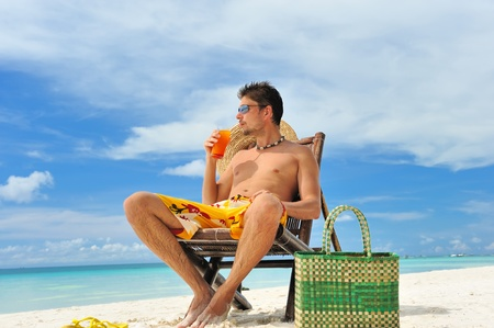 Man on a tropical beach with cocktail photo