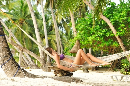 Woman in hammock on tropical beach photo