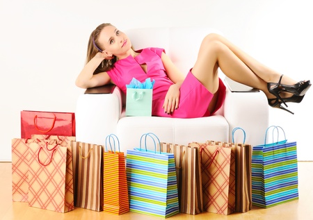 Woman with shopping bags having a rest on sofa photo