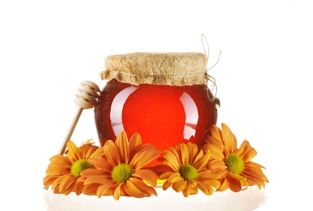 Jar of honey and dipper isolated over white Stock Photo - 9213349