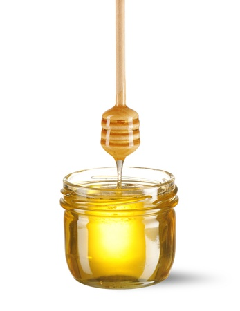 Jar of honey and dipper over white Stock Photo - 9213346