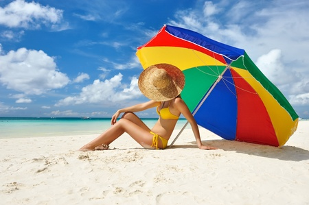 woman with umbrella: Girl on a tropical beach with hat Stock Photo