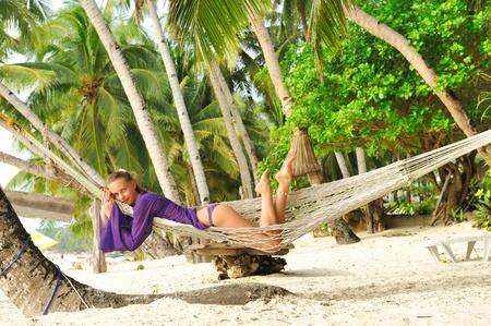 Woman in hammock on tropical beach photo