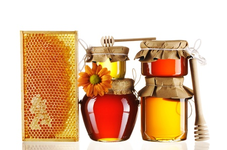 Jars of honey and dipper isolated over white photo