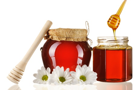 Jars of honey and dipper isolated over white