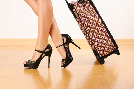 Womans legs and travel suitcase photo
