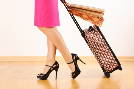 shopping trip: Womans legs and travel suitcase
