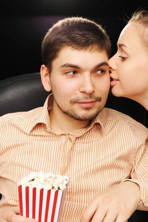 Young couple kissing at cinema photo