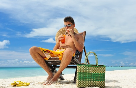Man on a tropical beach with cocktail Stock Photo - 9454385