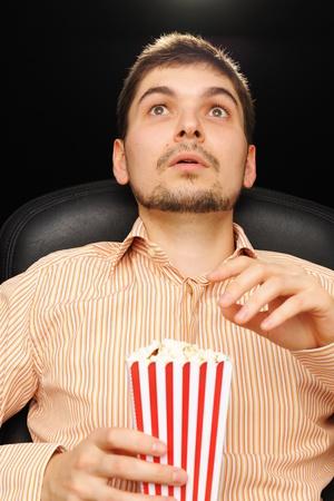 Young man watching movie at cinema photo