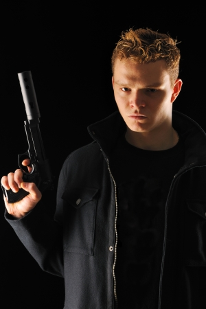 the silencer: Man holding gun with silencer over black