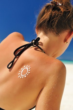 Sunscreen lotion over tan woman skin made as sun shape photo
