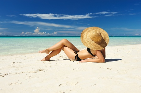 lying on back: Girl on a tropical beach with hat Stock Photo