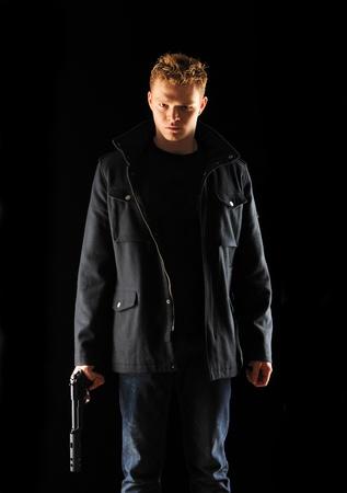 Man holding gun with silencer over black photo