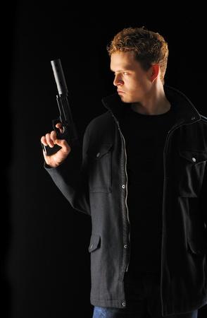 silencer: Man holding gun with silencer over black