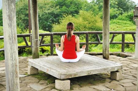 gazebo: Young woman practicing yoga outdoors