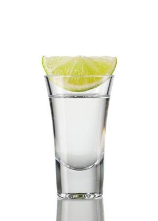 vodka: Tequila shot with lime isolated on white