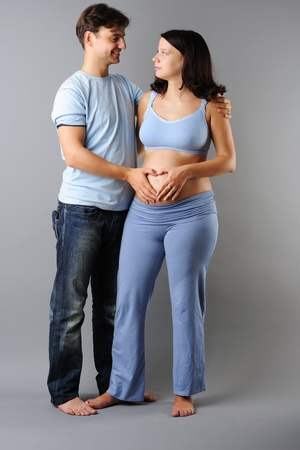Happy pregnant couple over grey background photo