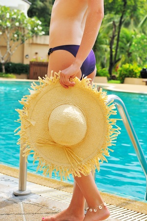Girl with hat in tropical swimming pool photo