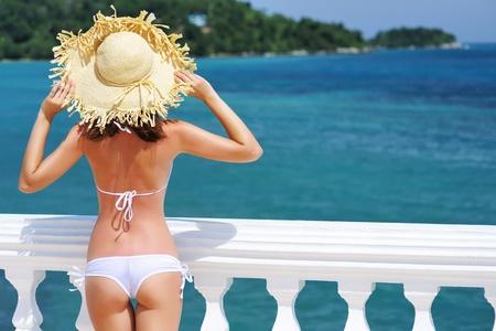 bikini butt: Girl on a tropical resort with hat Stock Photo