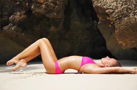 meuf sexy: Fille sur une plage tropicale rocheuse Banque d'images