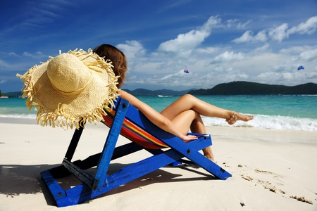 Girl on a tropical beach in chaise lounge photo