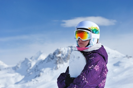 snowboard: Woman holding snowboard with mountains in background. No brandnames or copyright objects.  Stock Photo