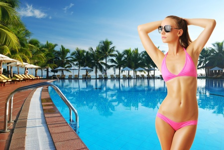 Girl with sunglasses at tropical swimming pool. Collage. Stock Photo - 12398691