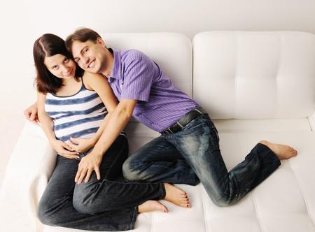 Happy pregnant couple on a sofa photo