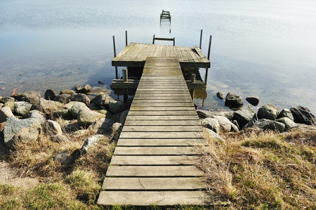 Old jetty wooden walkway pier on the lake photo
